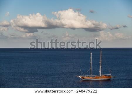 A beautiful old sailing boat in a peaceful blue sea. - stock photo