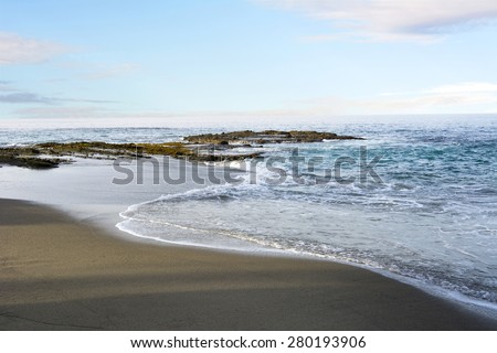 A beautiful pastel morning along a beach in Laguna California with gentle surf and a shoreline reef. B - stock photo