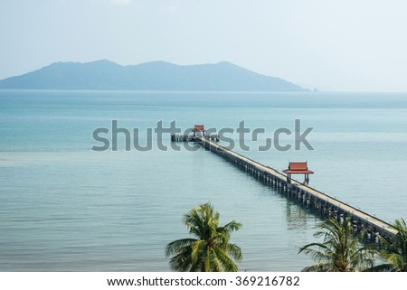 A beautiful pavilion in the sea with a cloudy sky and small mountains background - stock photo