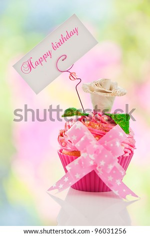 A beautiful pink happy birthday cupcake with flower and a label for your text as studio shot - stock photo