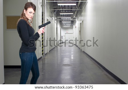 A beautiful police detective woman on the job with a gun - stock photo