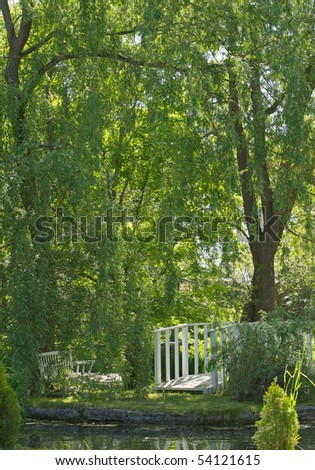 A beautiful pond under a weeping willow tree with a little bridge and bench in the summer. - stock photo