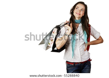 A beautiful portrait of a young attractive woman holding shopping bags and looking contemplative. Isolated over white.