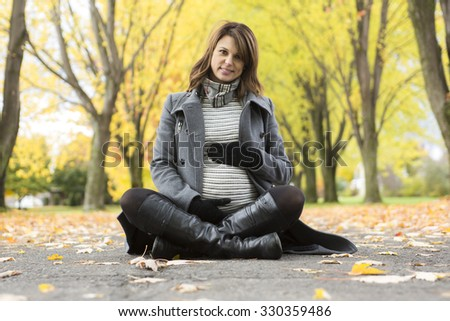 A Beautiful pregnant woman in the autumn park