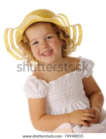 A beautiful preschooler in a white sundress and bright yellow hat. - stock photo