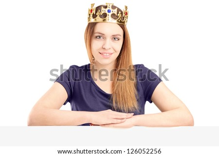 A beautiful queen with a golden crown posing behind a blank panel, isolated on white background - stock photo