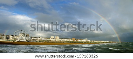 A beautiful rainbow appears in late afternoon sunshine over the East Beach in Brighton, UK - stock photo