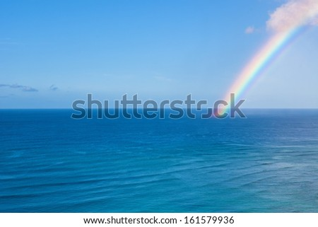 A beautiful rainbow graces the Pacific Ocean off Waikiki - stock photo