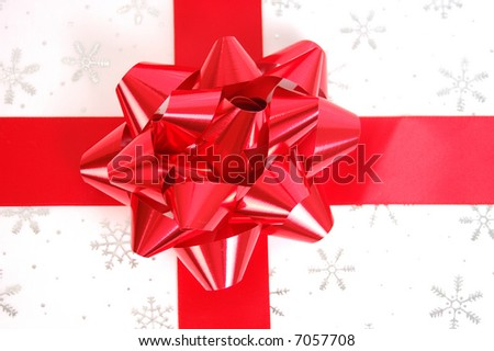 A beautiful red bow and ribbon on a snowflake covered package.