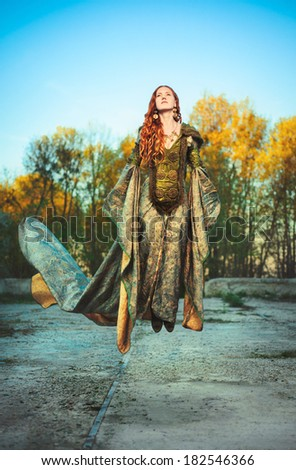 A beautiful red-haired lady in a luxurious royal dress rising to the sky - stock photo