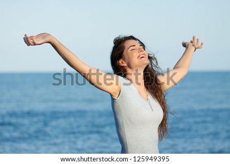A beautiful relaxed woman with arms stretched out standing on a beach.