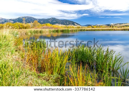A beautiful reservoir in autumn fields at the foot of the Bridger mountain range in Cherry Creek Nature Preserve on the outskirts of Bozeman, Montana - stock photo