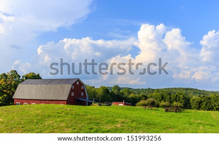 A beautiful rural scene with a red barn, farm fields and dramatic sky at sunset.