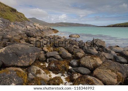 A beautiful sandy and rocky beach on the Isle of Barra in The Outer Hebrides - stock photo