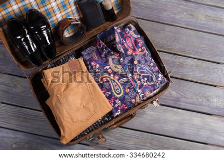 A beautiful set of men's clothing. Elegant clothes in the suitcase. - stock photo