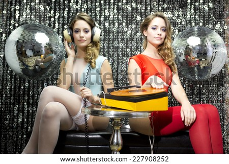 a beautiful sexy disco woman filmed twice in a bar lounge setting with record player and headphones - stock photo