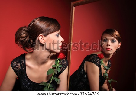 A beautiful sexy women wearing an evening dress and holding a red rose looking at her reflection in the mirror on red background - stock photo