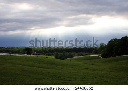 A beautiful sky over a country pasture with white fencing and horses grazing. - stock photo
