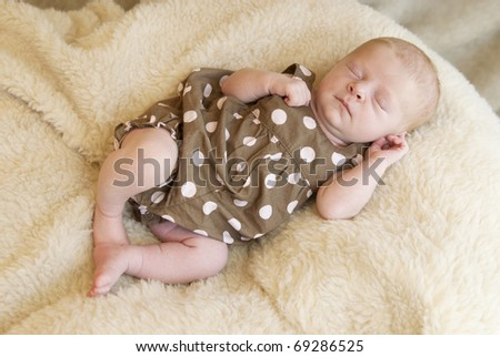 A beautiful sleeping baby girl on a blanket - stock photo