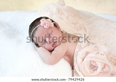 A beautiful sleeping newborn baby girl with a peach colored vintage lace scarf and flower headpiece