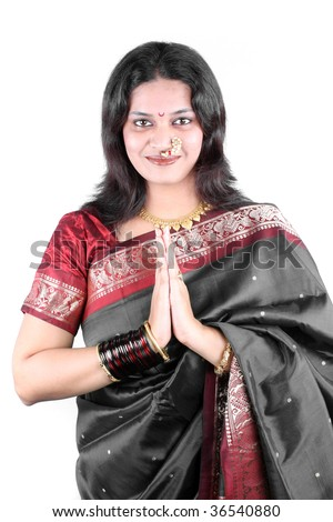 A beautiful smiling Indian woman in a traditional gray saree with a welcome gesture of Namaste, used in India like Hello in western countries. - stock photo