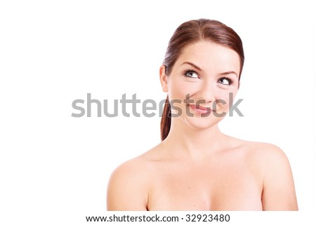 A beautiful smiling woman looking up to the side with copy space. Composition suggests she is topless.