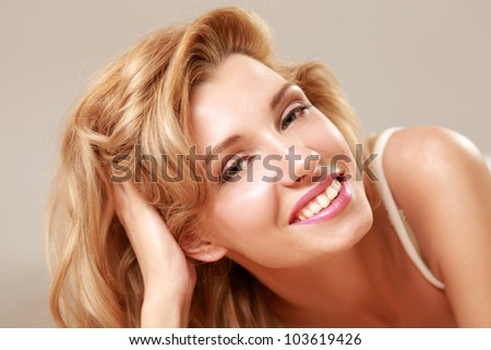 A beautiful smiling woman lying on bed, isolated on grey