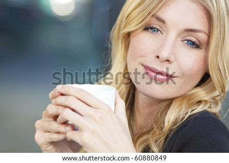 A beautiful smiling young woman with blond hair and blue eyes drinking coffee or tea from a white cup