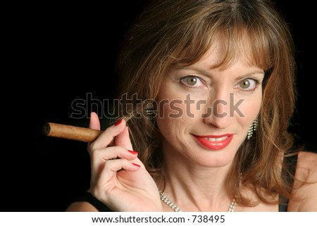 A beautiful, sophisticated woman with a cigar, against a black background. - stock photo