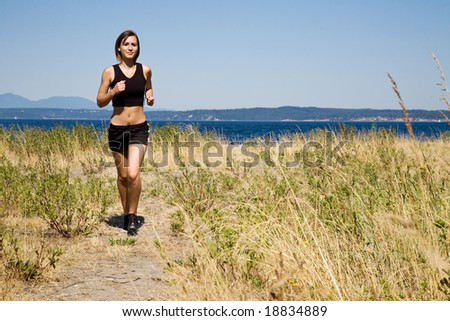 A beautiful sporty caucasian girl running on the beach - stock photo