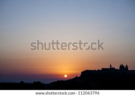 A beautiful summer sunrise over the medieval city of Mdina - stock photo