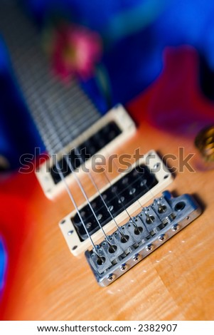 A beautiful sunburst colored electric guitar.  The bottom right edge of the guitar is in sharp focus with the rest of the guitar progressively blurred. Image has a bit of a soft focus effect. - stock photo