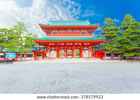 A beautiful sunny, blue sky behind the centered large red main Tower Gate Ro-Mon at the chinowa-kuguri decorated front entrance of Heian-Jingu Shinto Shrine in Kyoto, Japan. Horizontal - stock photo