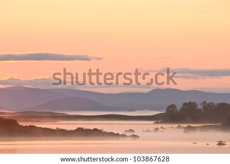 A beautiful sunrise on Rannoch Moor in Scotland with a great view over the moors with morning fog.
