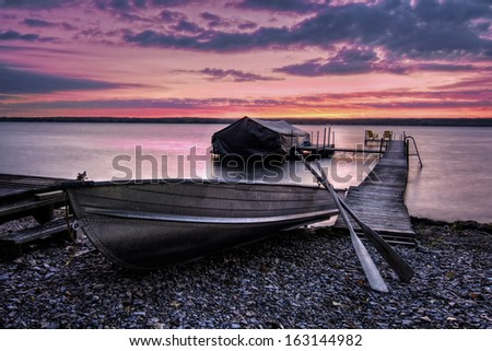 A beautiful sunrise on the shores of Lake Cayuga, Finger lakes region of New York state. A row boat sits on the side of a pier that leads out to a boat shelter and a deck for watching the sunrise. - stock photo