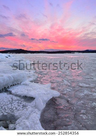 A beautiful sunset over a frozen lake with colorful light reflecting from shards of ice. - stock photo