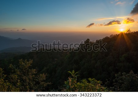 A beautiful sunset over the mountains and forests of the Doi Inthanon National Park in Northern Thailand - stock photo