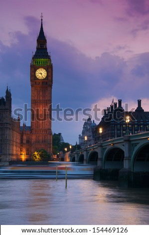 A beautiful sunset view of Big Ben and Westminster Bridge with a boat passing by - stock photo