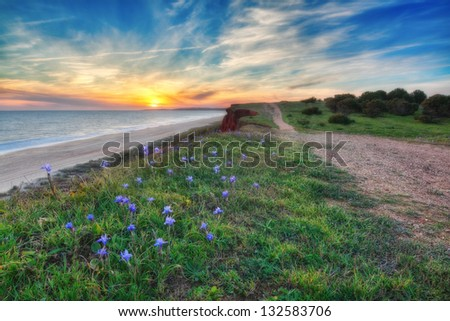 A beautiful sunset with sea and sky blue colors. Near the road. - stock photo