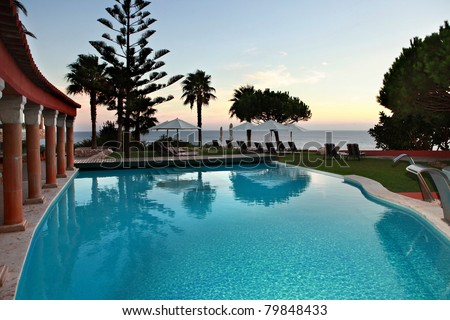 A beautiful swimming-pool in the coastline at dusk.