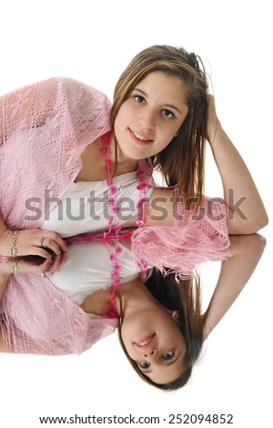 A beautiful teen girl happily relaxed on floor mirror.  On a white background.