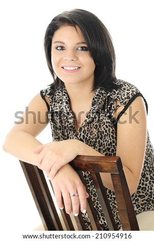 A beautiful teen girl happily sitting backwards on a wooden chair. - stock photo