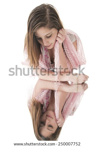 A beautiful teen girl looking at her image in a floor mirror.  On a white background.