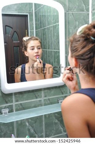 A beautiful teen girl putting lipstick and checking as she looks like. Teen girl happy with their appearance in the mirror using lipstick. - stock photo