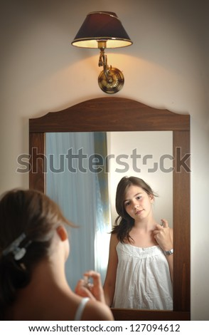 A beautiful teen girl studies her appearance as she looks into the mirror at her beautiful young reflection. Teen girl happy with their appearance in the mirror - stock photo