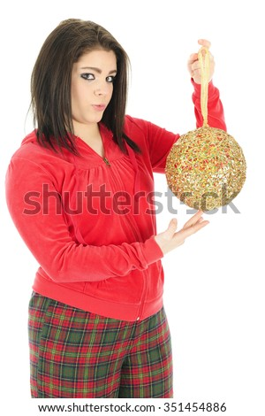 A beautiful teen girl wearing pajamas showing the viewer her favorite giant Christmas bulb. On a white background. - stock photo