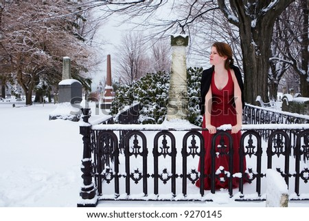 A beautiful teen grieving in a cemetery.  Cooling filter applied for ambiance. - stock photo