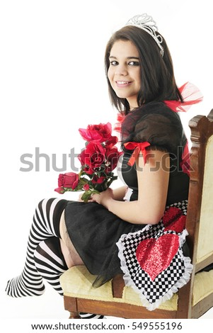 "A beautiful teen happily sitting in her black and red  ""Queen of Hearts"" dress looking back at the viewer while holding a bouquet of red roses.  On a white background."