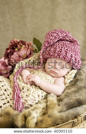 A beautiful three week old sleeping baby girl wearing a hat, selective focus - stock photo
