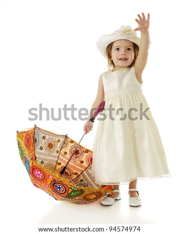 A beautiful toddler dressed up in white, waving hello with one hand while holding the handle of a brightly colored parasol in the other.  On a white background. - stock photo